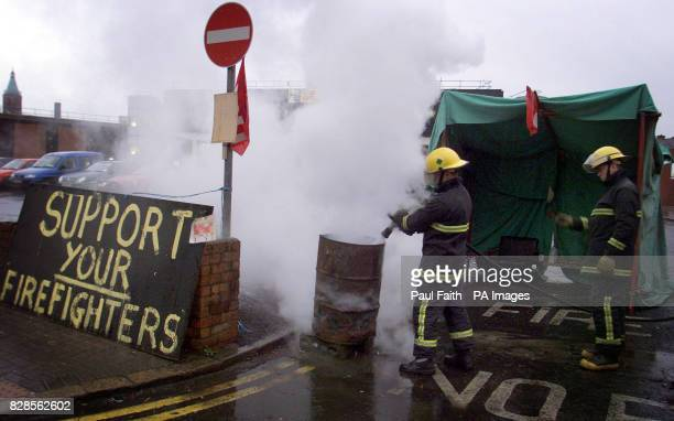 A Firefighter at Central Station in Belfast puts out the brazier in front of the station as the eight day nationwide strike comes to an end