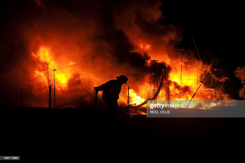 A firefighter attempts to extinguish a fire that engulfed a residential area in Manila on January 19, 2013. Almost 50 houses were destroyed leaving a hundred families homeless, according to local media reports. AFP PHOTO/NOEL CELIS