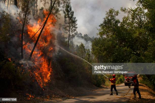 A firefighter battles a fire after a wildfire took dozens of lives on June 20 2017 in Mega Fundeira village near Picha in Leiria district Portugal On...