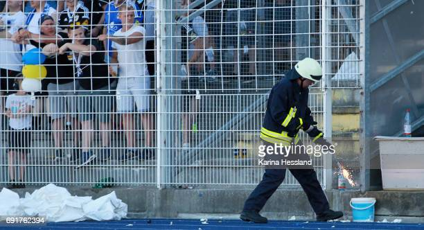 Firefighter brings Pyrotechnics to a bucket of water during the Third League Playoff Leg Two between FC Carl Zeiss Jena and Viktoria Koeln on June 01...