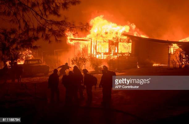 A firefighter carries a hose as a house burns in Oroville California on July 8 2017 The first major wildfires after the end of California's fiveyear...