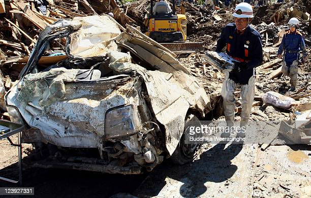 A firefighter carries documents found among the debris of houses destroyed by a landslide caused by heavy rain delivered by Typhoon Talas on...
