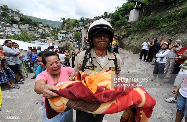 A firefighter carries the body of a baby who died in a landslide in the 14 de enero colony on the northern outskirts of Tegucigalpa following a...