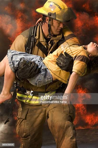 Firefighter carrying an injured boy