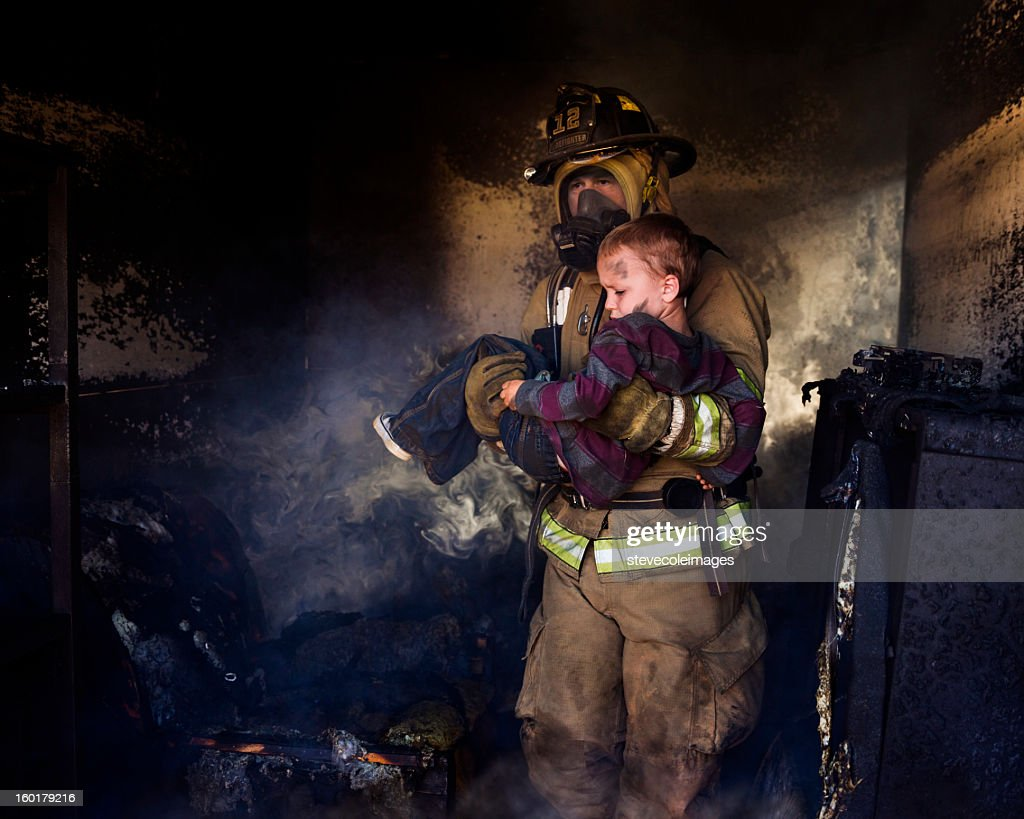 Firefighter Carrying Boy : Stock Photo