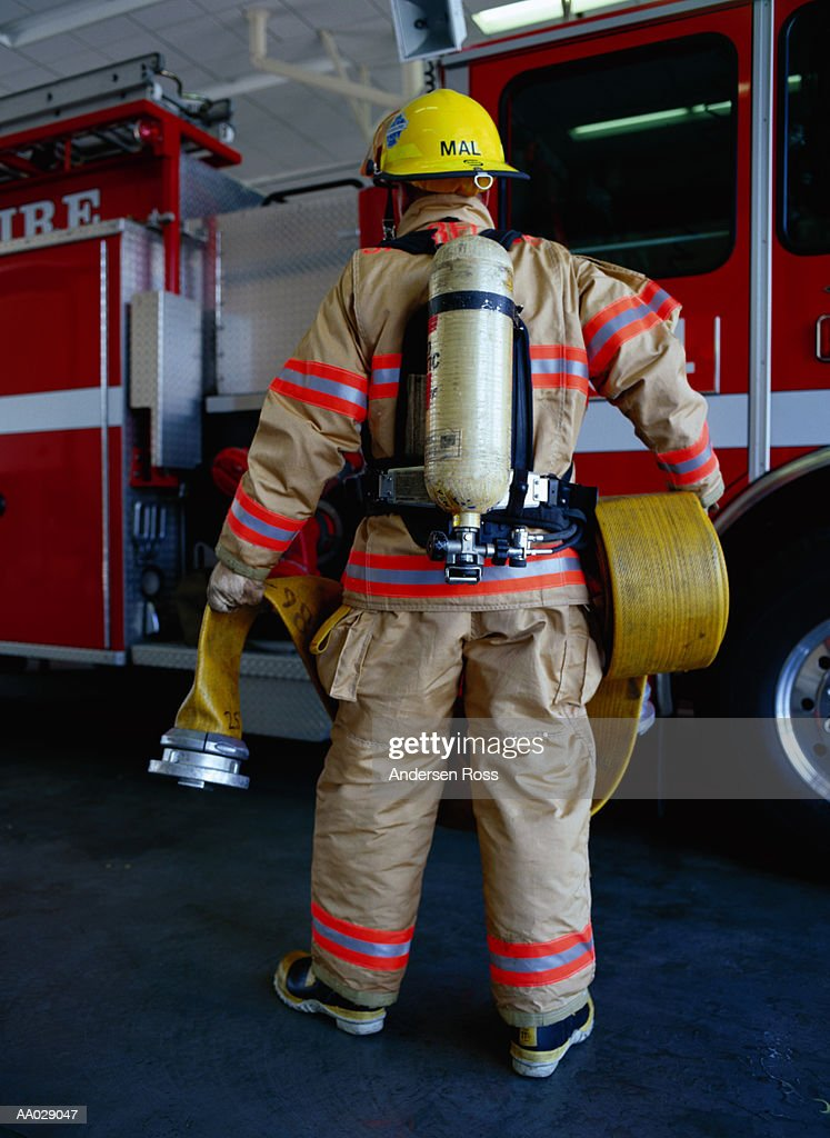 Firefighter carrying hose to fire engine, rear view
