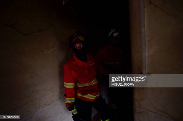 A firefighter checks a house in an area devastated by a wildfire in Canical near Alvares on May 18 2017 Portugal declared three days of national...