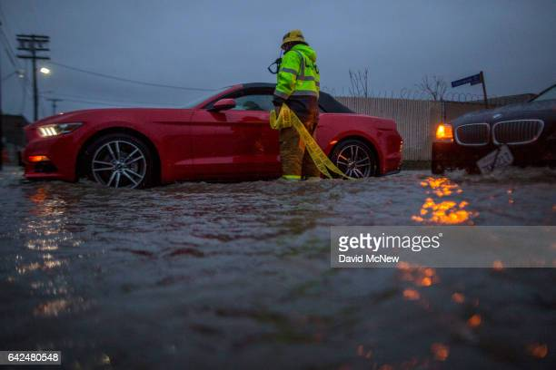 A firefighter checks on stalled cars in a flooded street as a powerful storm moves across Southern California on February 17 2017 in Sun Valley...