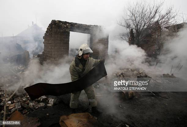 A firefighter clears debris in Avdiivka after heavy shelling by proRussian rebels on February 25 2017 Sixteen Ukrainian soldiers were wounded within...