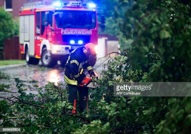 A firefighter clears the road after a storm on June 22 2017 in Ebstorf / AFP PHOTO / dpa / Philipp Schulze / Germany OUT