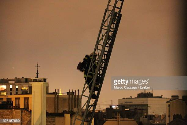 Firefighter Climbing Ladder With Buildings Against Sky