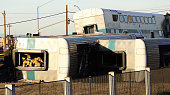 A firefighter climbs out an overturned Metrolink train car that derailed after colliding with a vehicle on the tracks February 24 2015 in Oxnard...