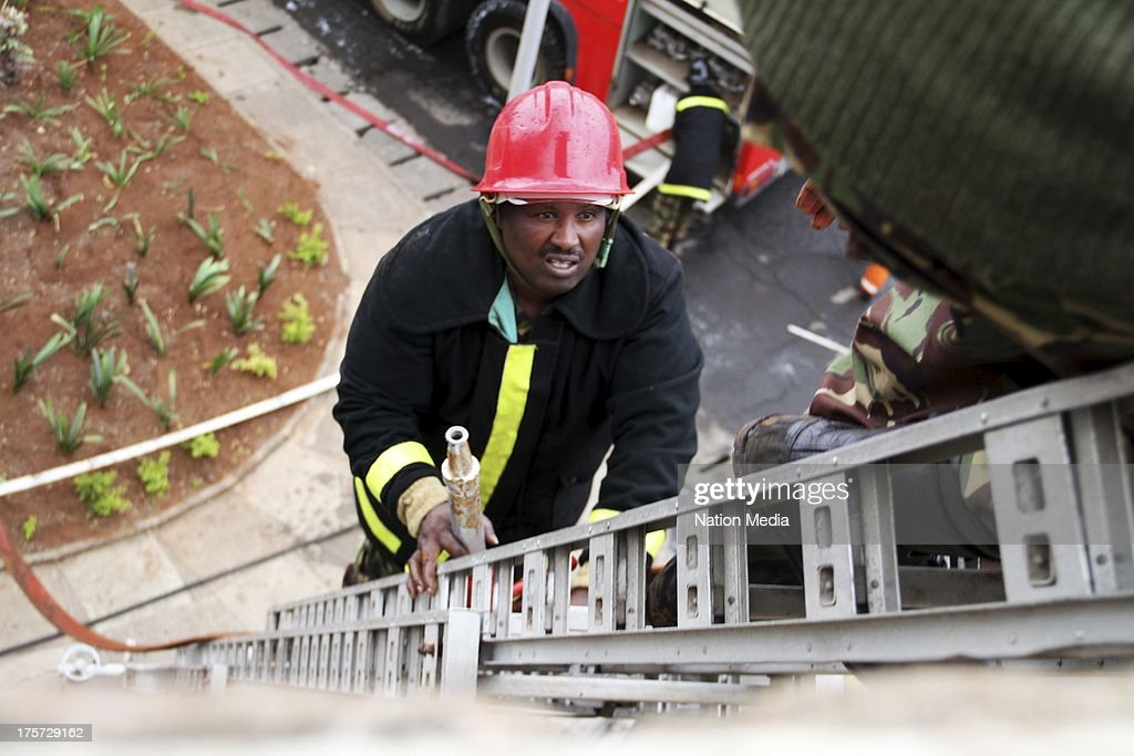 (Not for sale to The Star (Kenya), Capital FM, The People, Citizen TV, Kenya Broadcasting Corporation)A firefighter climbs up a ladder with a hose at the Jomo Kenyatta International Airport (JKIA) International Arrivals section on August 06, 2013 in Nairobi, Kenya.