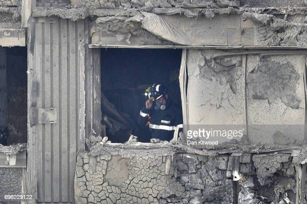 A firefighter conducts a search of burned out flat in Grenfell Tower on June 15 2017 in London England At least 17 people have been confirmed dead...