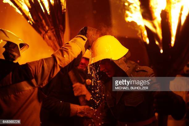Firefighter cool a helmet with water as a man carries burning bundles of pinewood chips on their shoulders during the 'Chienbase' procession on March...