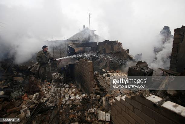 A firefighter douses a fire in Avdiivka after heavy shelling by proRussian rebels on February 25 2017 Sixteen Ukrainian soldiers were wounded within...