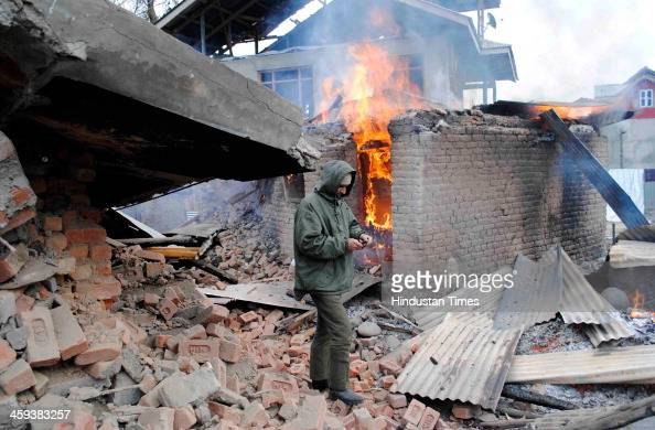 Firefighter douses flames after a house caught fire during an encounter at Hushroo Chadoora in Central Kashmir Budgam district 30 Km from Srinagar...