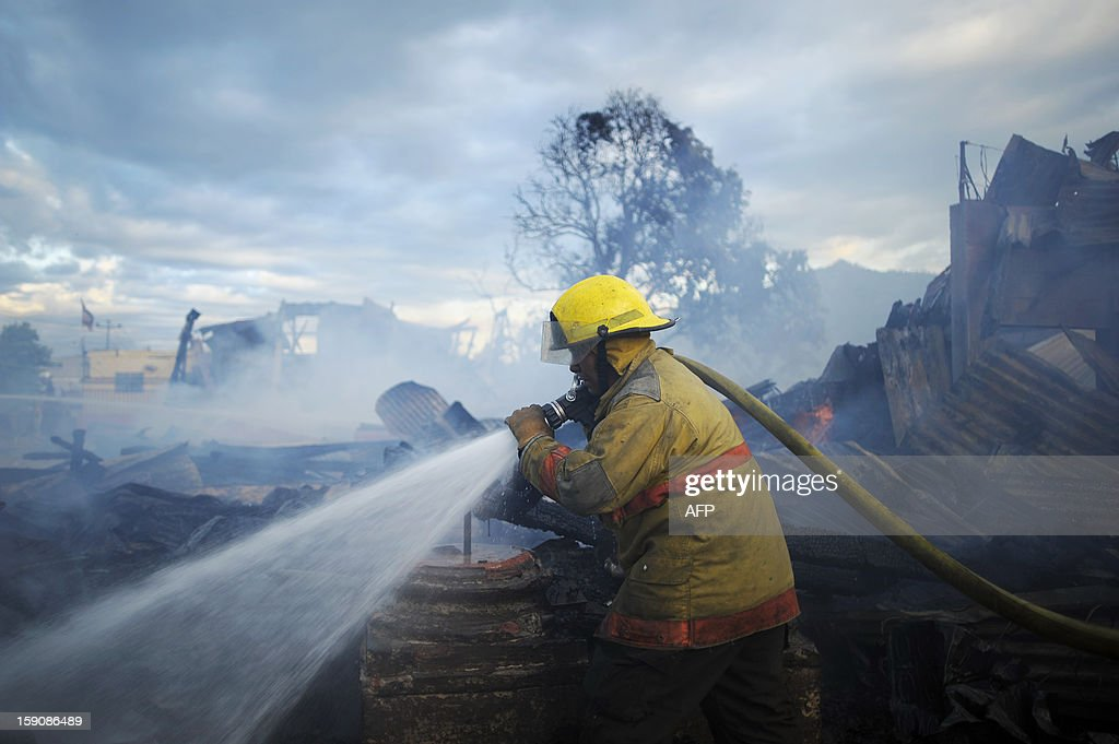 A firefighter douses smouldering rubble following a blaze that destroyed the San Esteban Church, an historical landmark in downtown San Salvador, El Salvador on January 7, 2012. The San Esteban was built in the 19th century in Belgium, transported and assembled in one of the oldest localities of the capital city. AFP PHOTO/ Jose CABEZAS