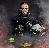 A professional firefighter dressed in uniform holding safety helmet in fire sparks and smoke over a dark background.