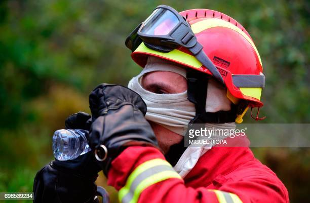 A firefighter drinks water as they combat a wildfire in Vale da Ponte Pedrograo Grande on June 20 2017 The huge forest fire that erupted on June 17...