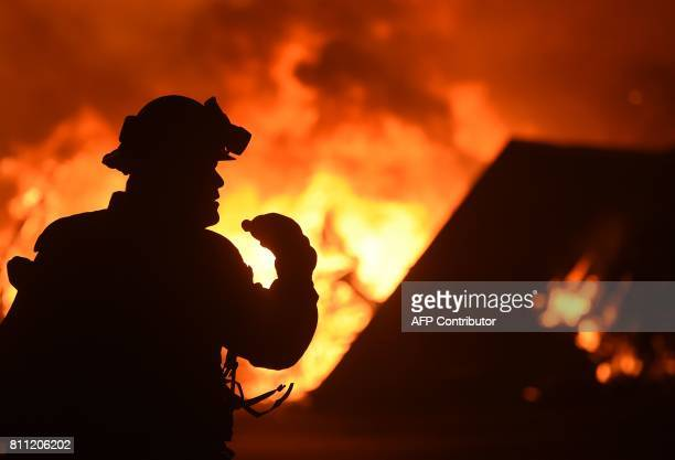 A firefighter drinks water in front of a burning house near Oroville California on July 9 2017 The first major wildfires after the end of...