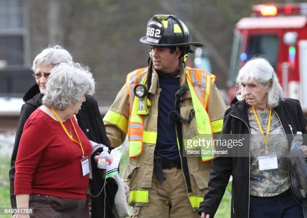 A firefighter escorts passengers from a charter bus with minor injures walk to a waiting school bus after their bus was hit by a CSX train at the...