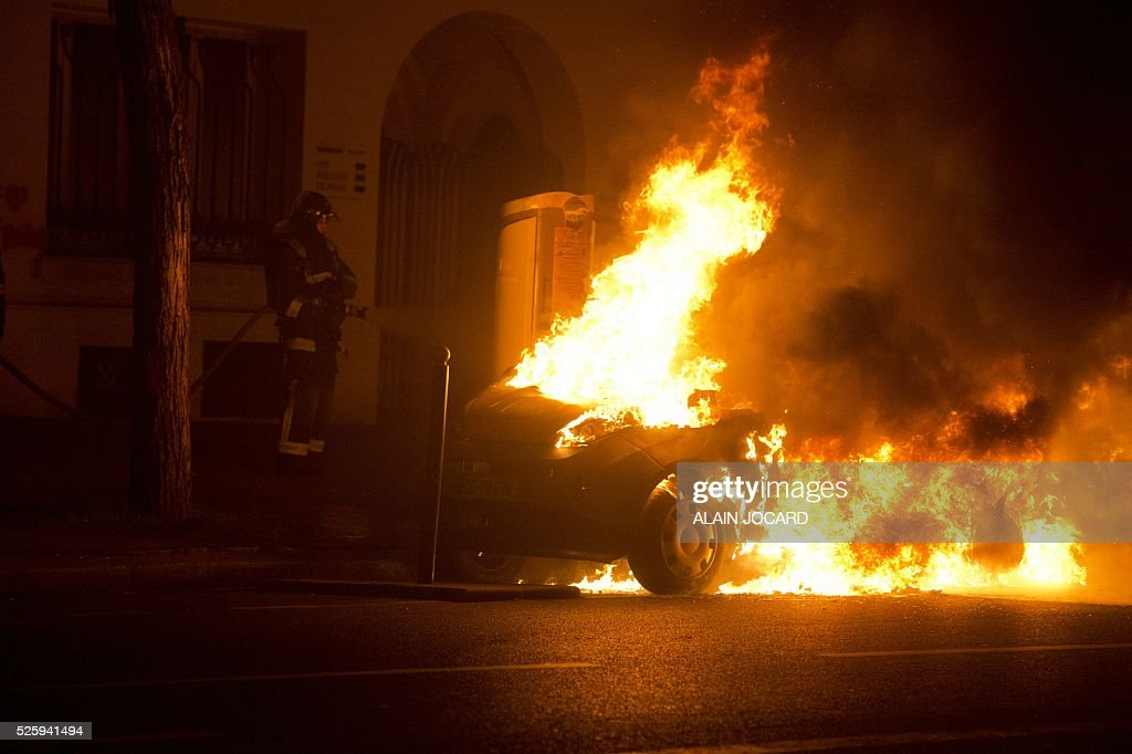 A firefighter extinguishes a burning car as French riot police clear the Place de la Republique in Paris during a protest by the Nuit Debout, or 'Up All Night' movement who have been rallying against the French government's proposed labour reforms on April 29, 2016. People were arrested and others detained during the overnight clashes in the French capital as the police dispersed the protesters whose movement began on March 31 in opposition to the government's proposed labour reforms. / AFP / ALAIN