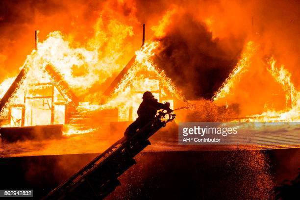 TOPSHOT A firefighter extinguishes a fire at Kandawgyi Palace hotel in Yangon early on October 19 2017 One person died in a predawn blaze on October...