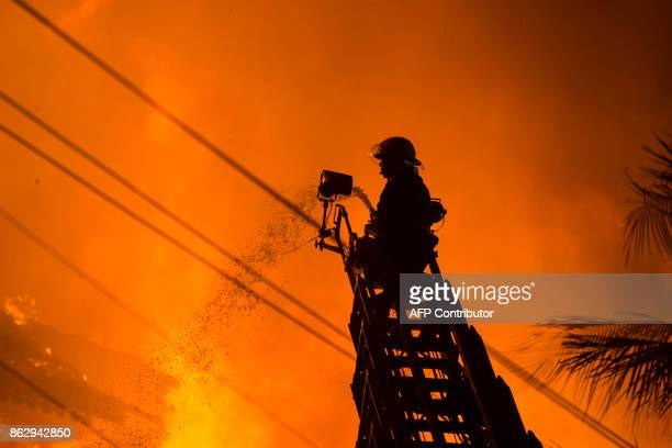 A firefighter extinguishes a fire at Kandawgyi Palace hotel in Yangon early on October 19 2017 One person died in a predawn blaze on October 19 that...