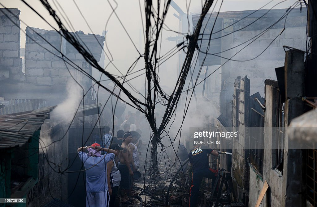A firefighter (R) extinguishes remaining flames after a pre-dawn fire engulfed a slum area in Manila on December 25, 2012. At least seven people were killed and thousands left homeless as two fires struck the Philippine capital on Christmas Day, sparking riots as a slum went up in flames, Manila's fire marshal said.