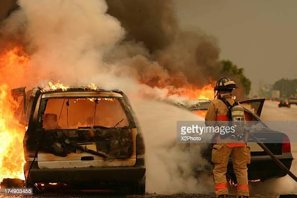 Firefighter extinguishing burning vehicle