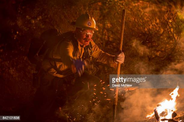 A firefighter fights flames in chaparral brush using only a hand tool at the La Tuna Fire on September 2 2017 near Burbank California Los Angeles...