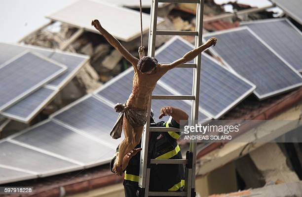 TOPSHOT A firefighter fixes a crucifix in Amatrice central Italy on August 30 prior to a funeral ceremony for the victims of a recent earthquake The...