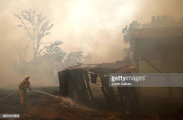 A firefighter from Kentfield California sprays water on an out building that started to burn during a back fire operation while battling the Rocky...