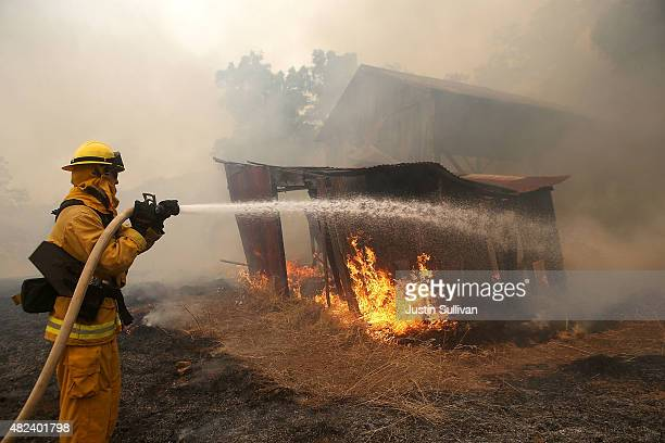 A firefighter from Kentfield California sprays water on an outbuilding that started to burn during a back fire operation while battling the Rocky...
