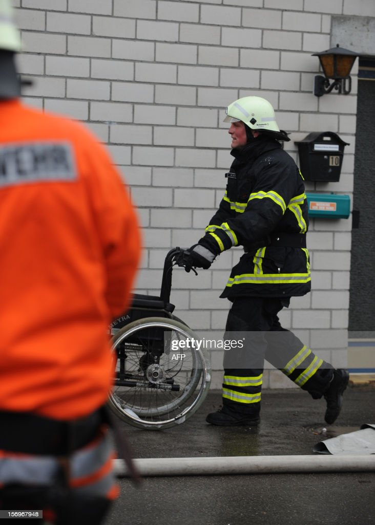 A firefighter goes to house with a workshop for handicapped people in Titisee- Neustadt, southern Germany on November 26, 2012. Fourteen people died after a fire broke out. AFP PHOTO / PATRICK SEEGER GERMANY OUT