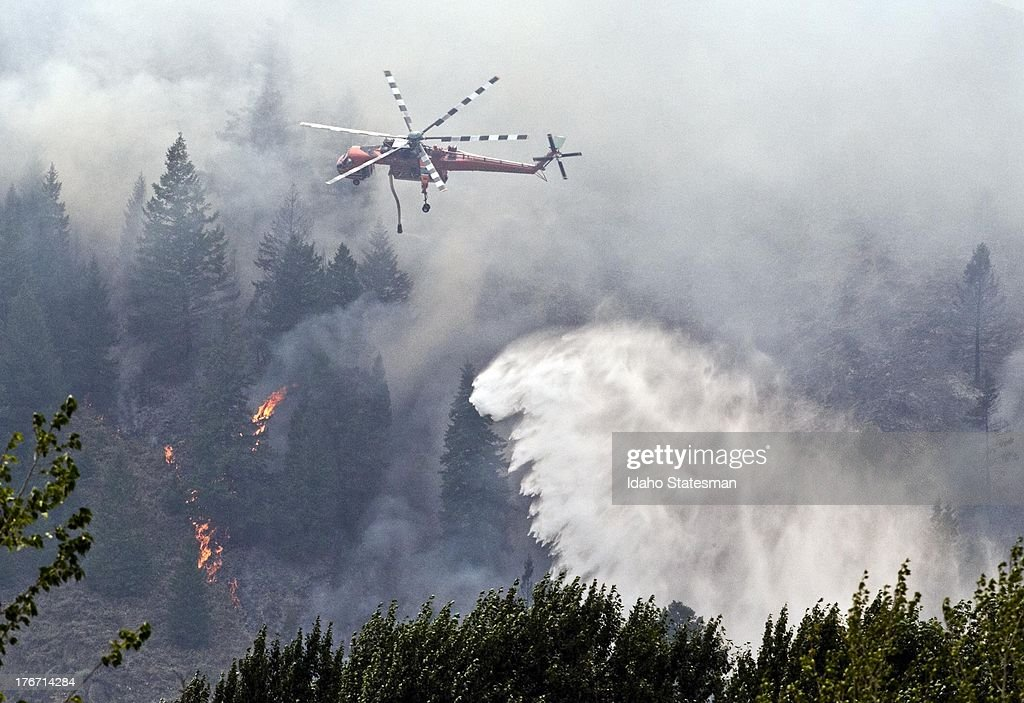 A firefighter helicopter continues to battle the Beaver Creek Fire in the Wood River Valley, as it drops water on the canyon hillside west of Hailey, Idaho, Saturday.