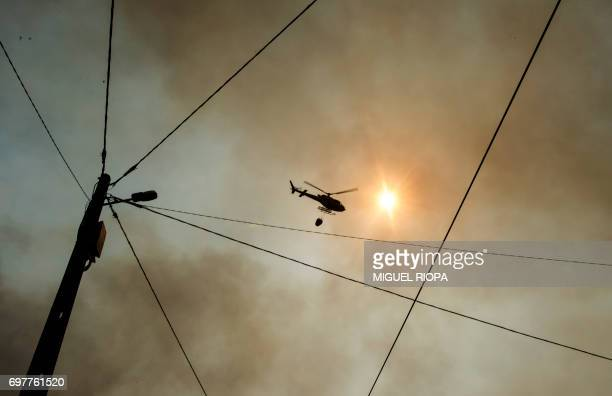 TOPSHOT A firefighter helicopter overflies a wildfire in Carvalho next to Pampilhosa da Serra on June 19 2017 More than 1000 firefighters are still...