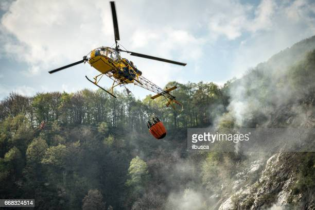 Hélicoptère de pompier éteindre un feu sur la forêt de montagne