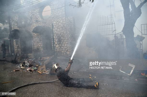 TOPSHOT A firefighter help to fight a fire in the commune of Petion Ville PortauPrince on April 4 2016 The fire destroyed a hotel a house and several...