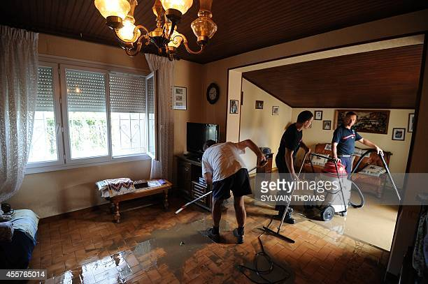 A firefighter helps inhabitants to clean their splintered house in the northern neighborhood of Ales central France on September 20 after heavy rains...