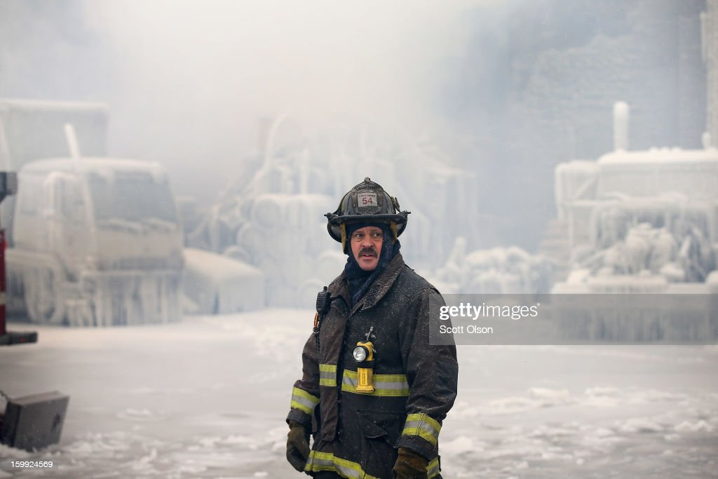 A firefighter helps to extinguish a massive blaze at a vacant warehouse on January 23, 2013 in Chicago, Illinois. More than 200 firefighters battled a five-alarm fire as temperatures were in the single digits.