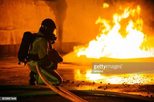 Feuerwehrmann hält Schlauch und Besprühen mit Wasser