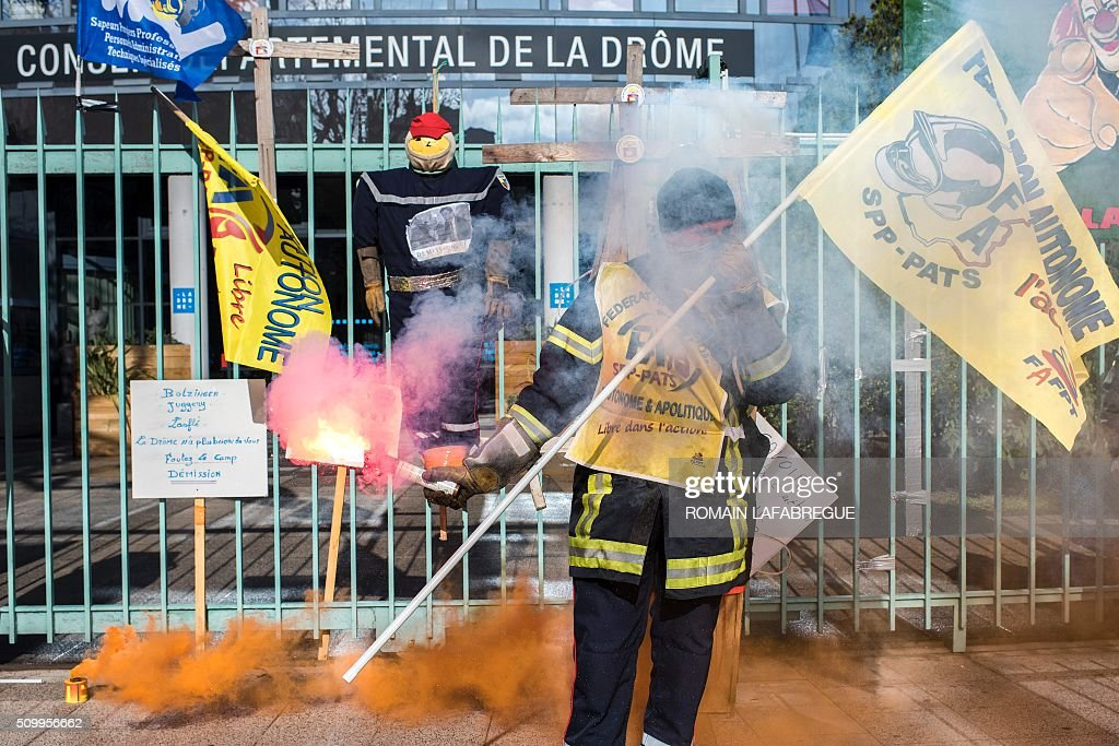A firefighter holds a flare during a demonstration in front of the Drome departemental council in Valence, central eastern France, on February 13, 2016, to protest against staffing cuts and the closure of 19 fire stations. / AFP / ROMAIN LAFABREGUE