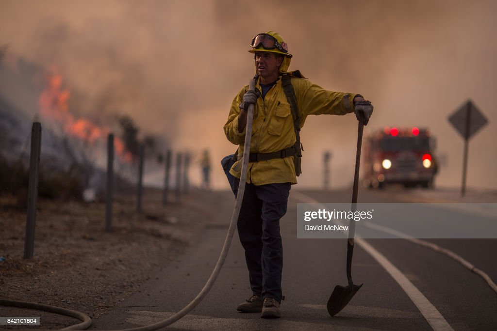 A firefighter holds a hose on the 120 freeway during the La Tuna Fire on September 2, 2017 near Burbank, California. Los Angeles Mayor Eric Garcetti said at a news conference that officials believe the fire, which is at 5,000 acres and growing, is the largest fire ever in L.A. People have been evacuated from hundreds of homes in Sun Valley, Burbank and Glendale. About 100 Los Angles firefighters are expected to return soon from Texas, where they've been helping survivors from Hurricane Harvey.