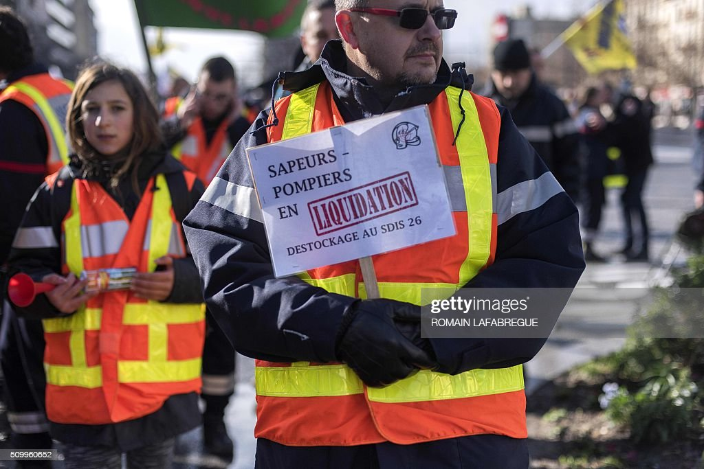 A firefighter holds a placard reading 'Liquidation of firefighters, destock of the SDIS 26' during a demonstration in Valence central eastern France, on February 13, 2016, to protest against the closure of 19 emergency services and fire centers. / AFP / ROMAIN LAFABREGUE