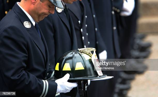 A firefighter holds the helmet of firefighter Joseph Graffagnino at his funeral August 23 2007 in the Brooklyn borough of New York City Joseph...