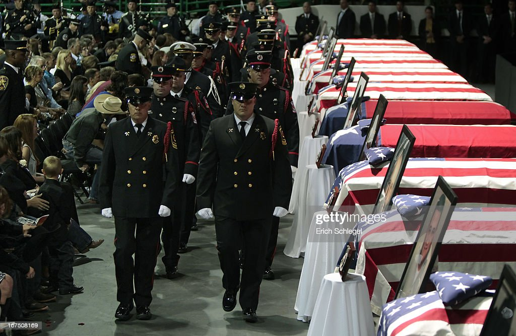 A firefighter honor guard marches past the caskets of the 12 fallen volunteer firefighters at the West memorial service held at Baylor University April 25, 2013 in Waco, Texas. The memorial service honored the volunteer firefighters that lost their lives at the fertilizer plant explosion in West, Texas last week.