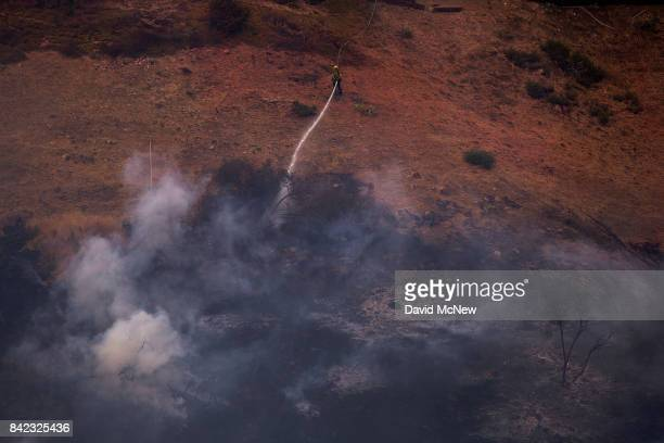 A firefighter hoses down a hot spot below him from a section of hillside covered with PhosChek fire retardant during the La Tuna Fire on September 3...