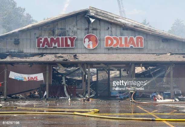 A firefighter hoses down a hot spot outside the Family Dollar store Sunday July 16 2017 in Waterboro Maine A fire destroyed three businesses in the...